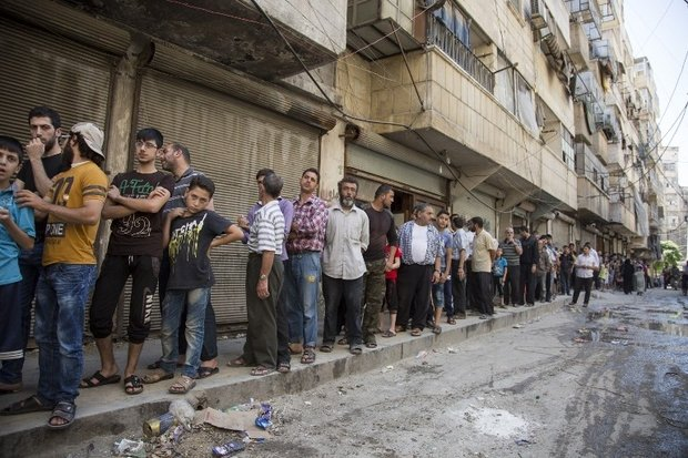 Syrians queue up to buy bread in a rebel held neighborhood on July 12, 2016. PHOTO AFP/ KARAM AL-MASRI